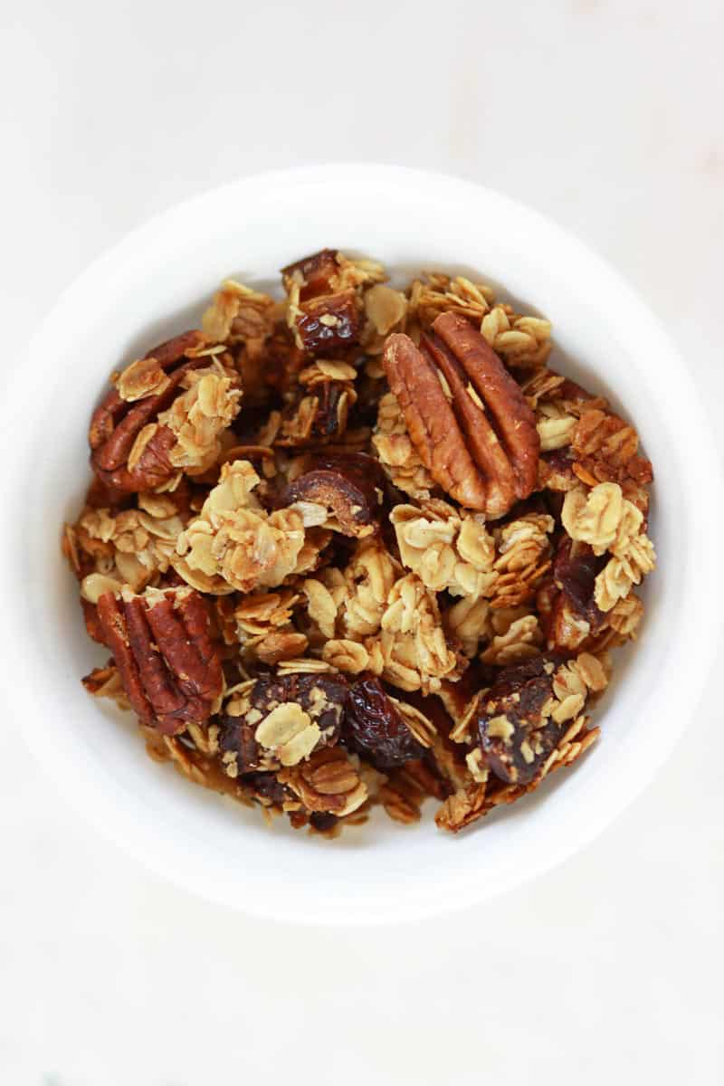a small bowl of homemade granola with dates and pecans in it