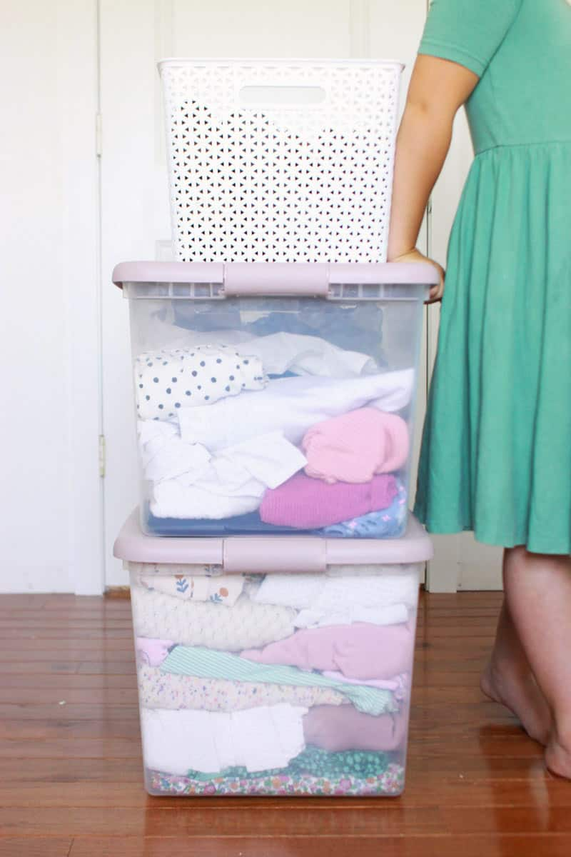 a girl in a teal dress next to a stack of clothes storage totes