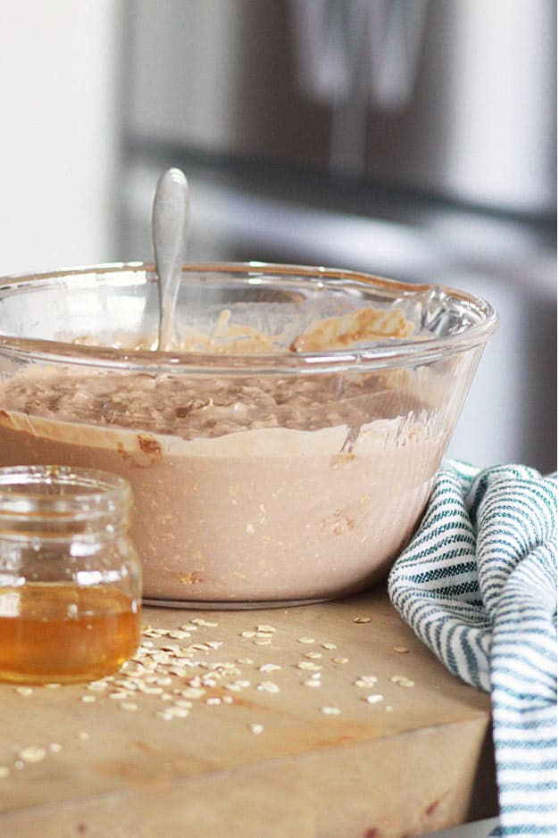 a bowl full of chocolate overnight oats with a small jar of honey next to it