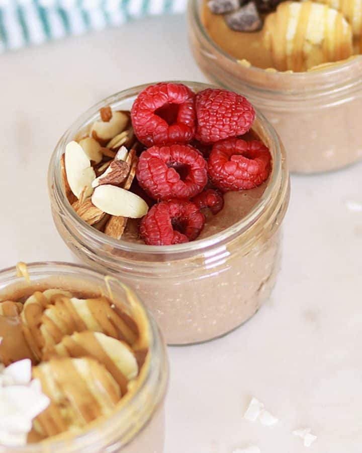 3 mason jars of chocolate overnight oats topped with raspberries and bananas