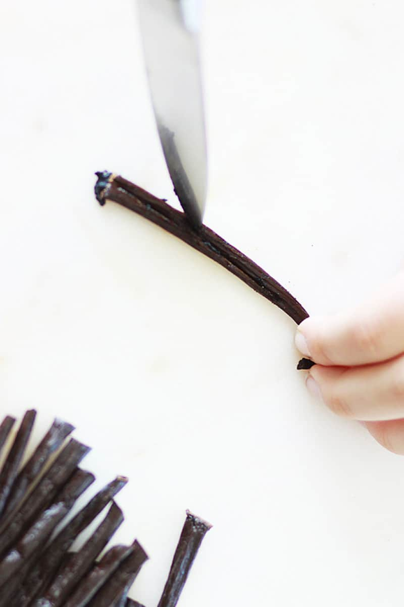 a knife slicing vanilla beans down the center