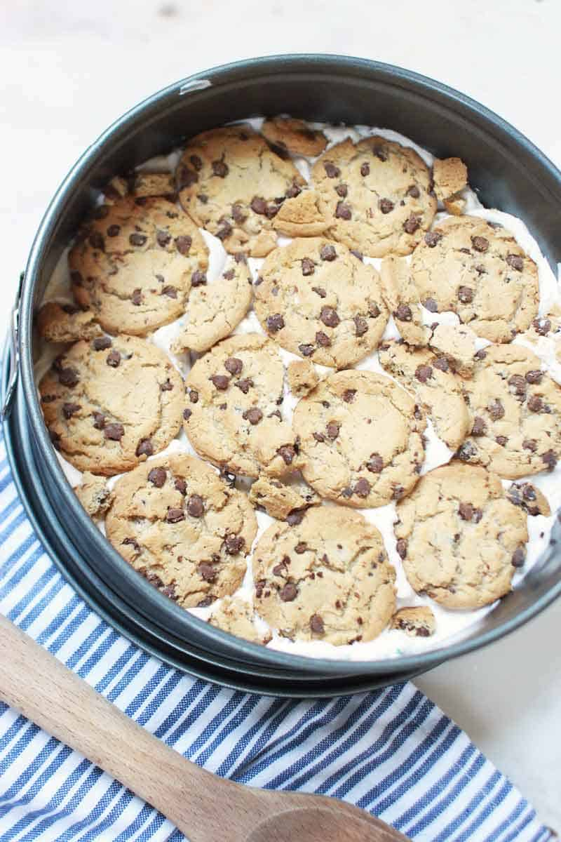 a layer of chocolate chip cookies on a layer of cream in a spring form pan