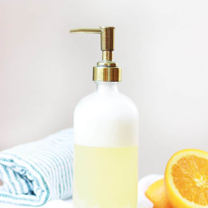 a glass bottle with face wash and a brass pump top. an orange and a striped bath towel are in the background