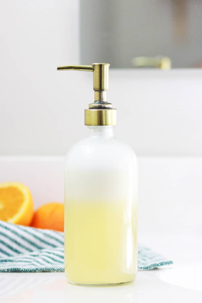 a glass bottle of homemade orange face soap with a cut orange and striped towel in the backgroung