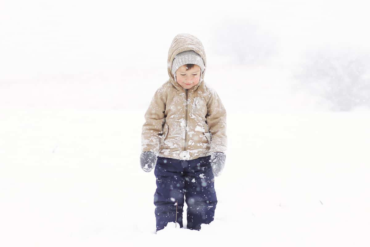 a little boy standing in the snow wearing snow pants, coat, hat and mittens