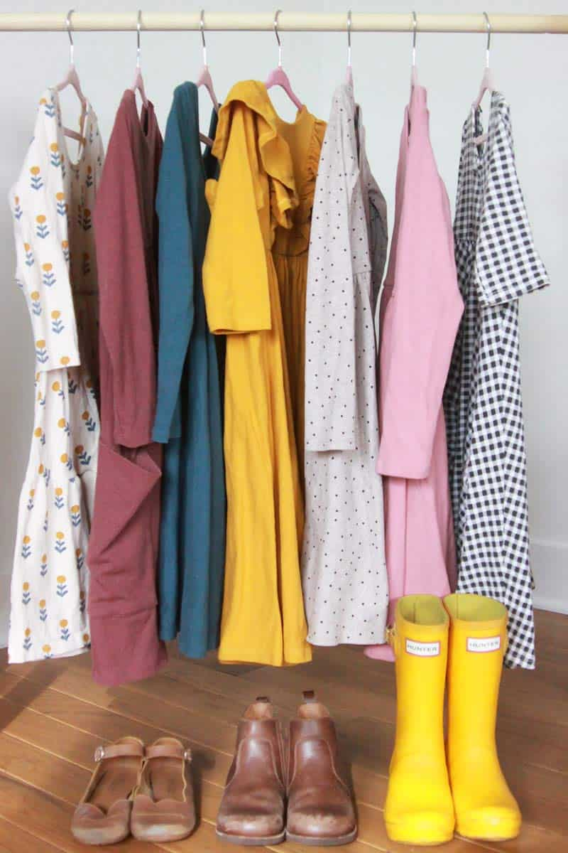 a clothes rack of little girl Fall dresses and shoes making up a capsule wardrobe