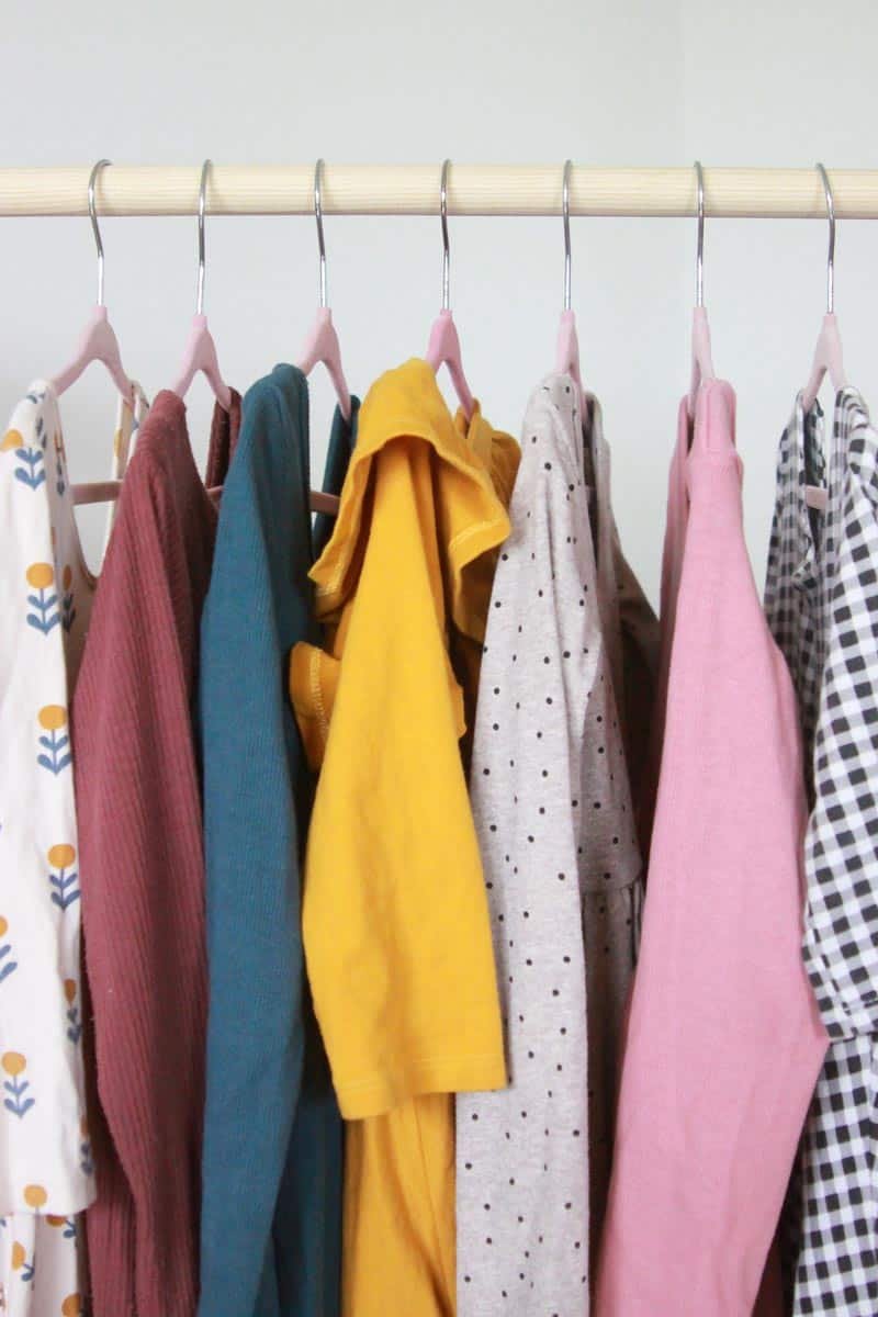a bunch of little girl dresses hanging up together