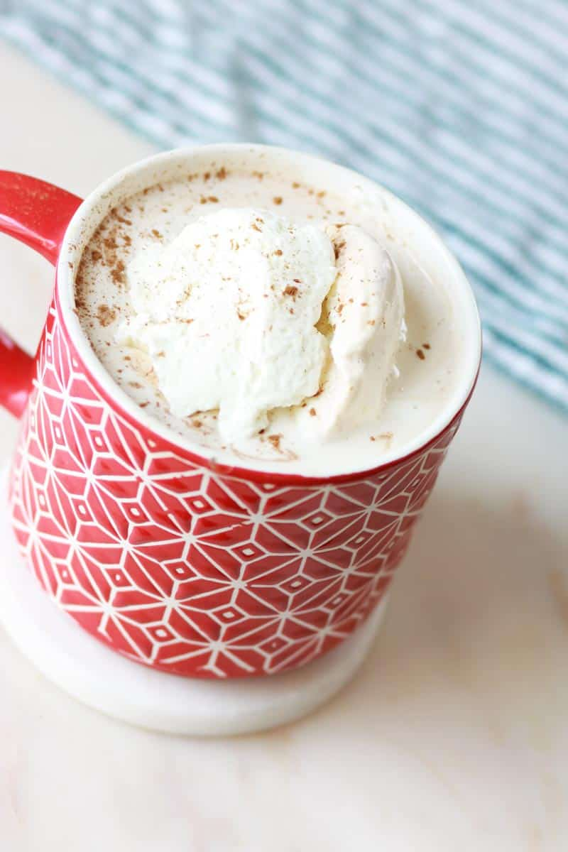 a red mug of homemade cocoa with whipped cream on top