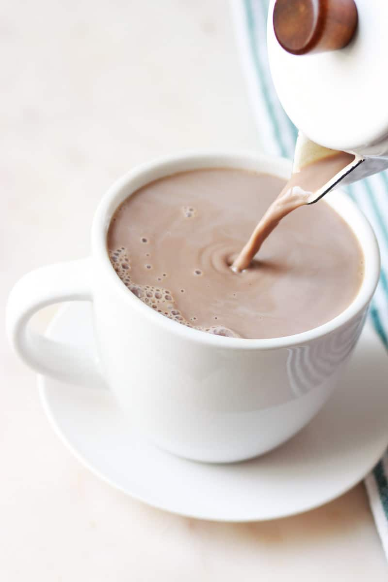 homemade cocoa being poured out of a cocoa pot into a white hot cocoa cup