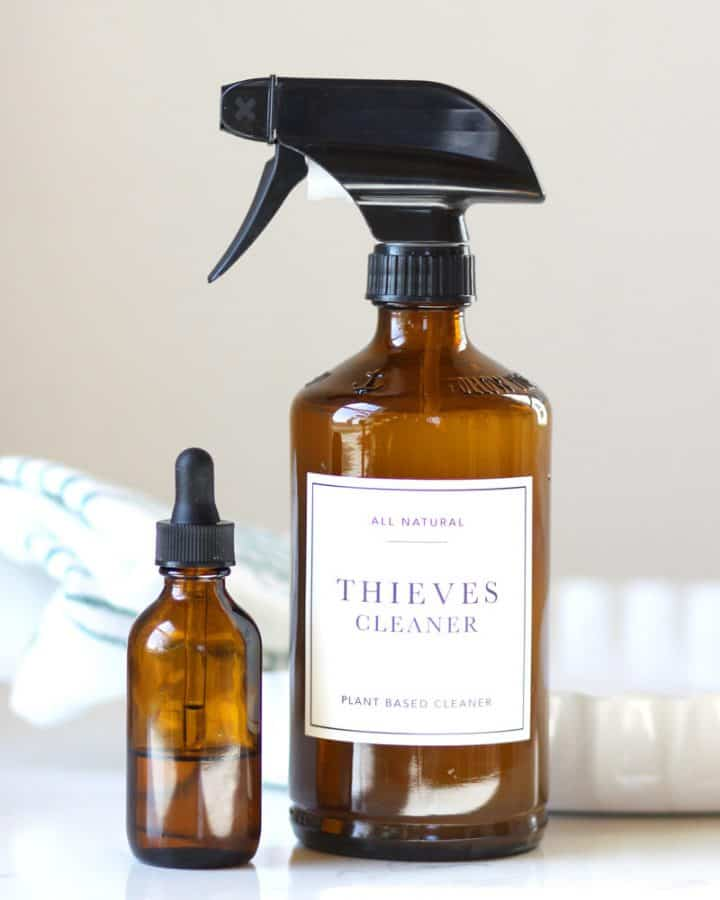 """an amber glass spray bottle with a label that says """"thieves cleaner"""" on it and some amber essential oil bottles on a counter"""