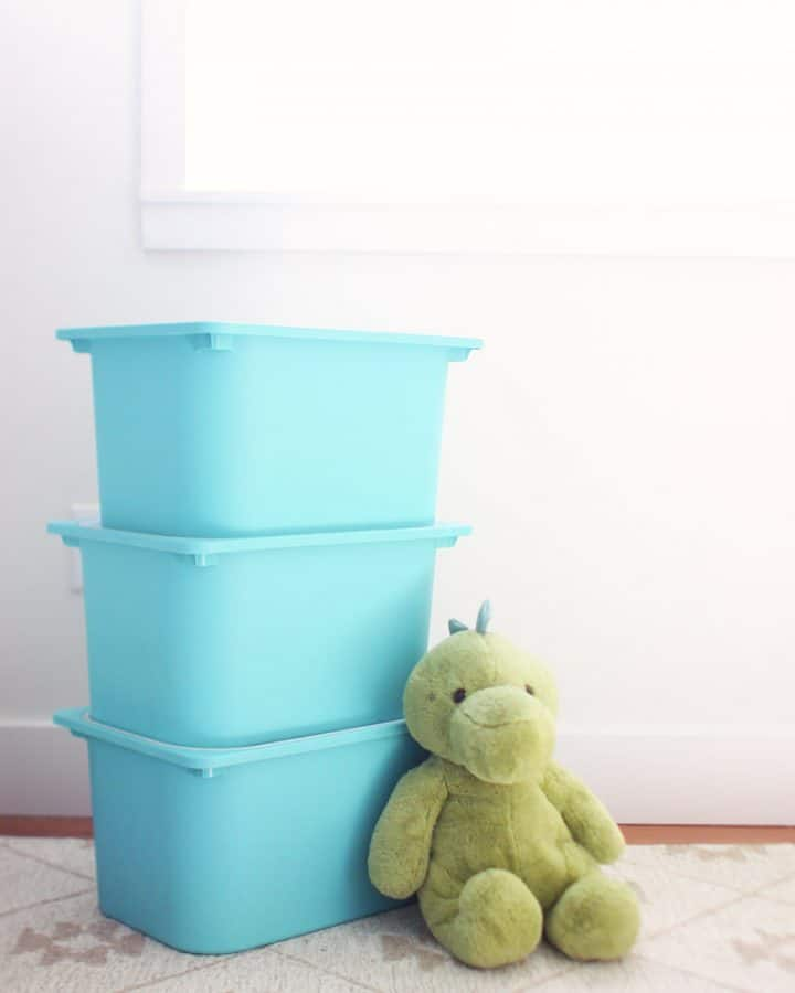 3 plastic ikea toy bins stacked on top of eachother with a stuffed green dragon leaning against them
